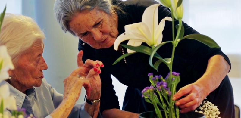 Mujeres mayores cuidan de unas flores