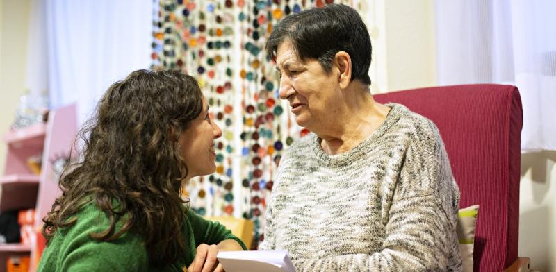 Una mujer mayor conversa con una mujer joven en su domicilio