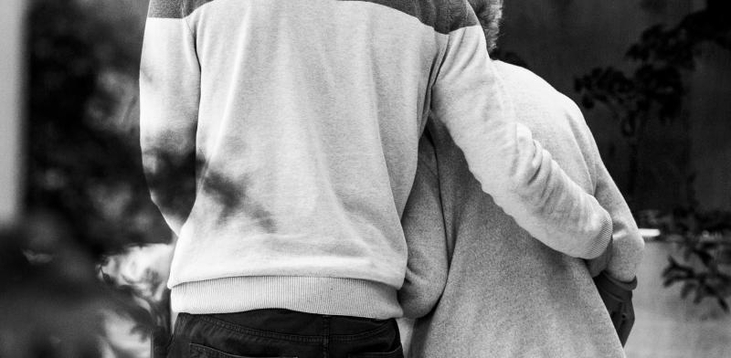 Persona joven ayuda a caminar a una mujer mayor