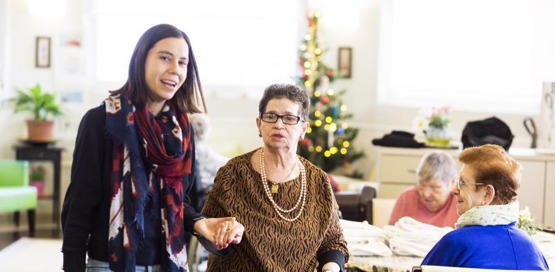 Mujer joven acompañando a una mujer mayor de la mano