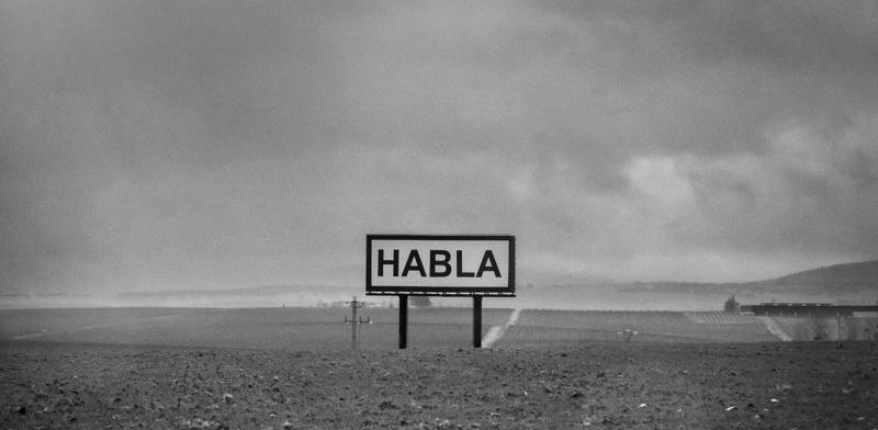 """Cartel anunciador en medio de un campo con el mensaje: """"habla"""""""