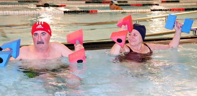 Personas haciendo ejercicio en una piscina cubierta
