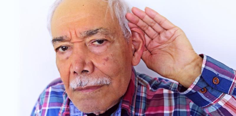 Persona llevándose una mano al oído en un gesto de que no oye bien