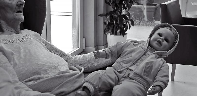 Mujer mayor dormida sosteniendo una muñeca