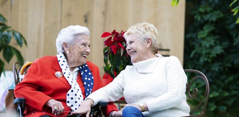 Mujer mayor y su familiar se miran y sonríen