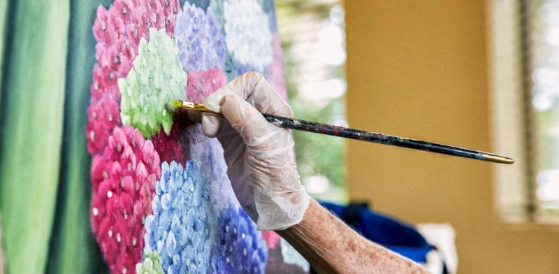 Mano con un pincel pintando un lienzo de unas flores