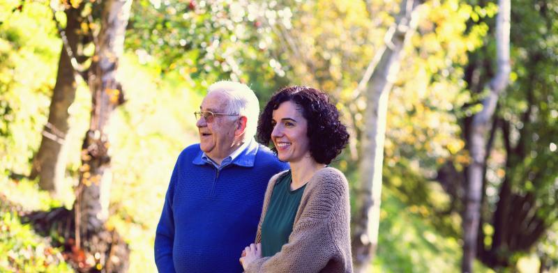Persona mayor pasea acompañado de una cuidadora